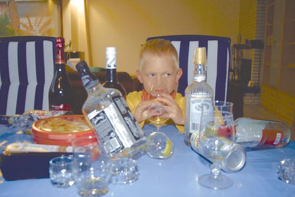 Kind zwischen leeren Gläsern und Flaschen trinkt AlLkohol