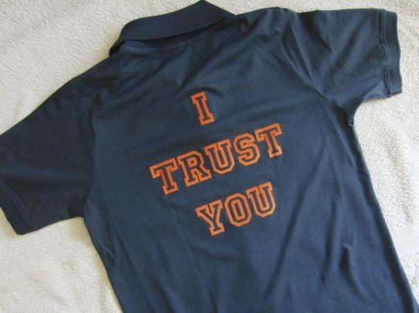Polohemd mit der Aufschrift 'I Trust You' auf dem Rücken