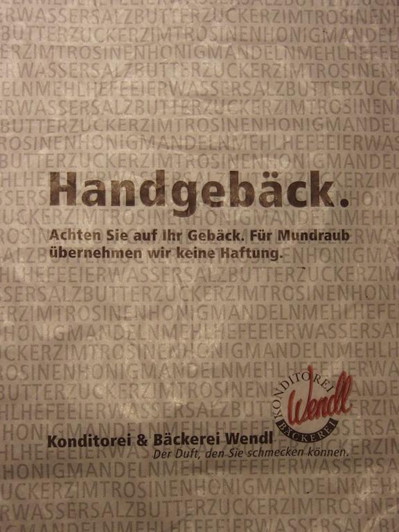 """Papiertüte einer Bäckerei mit der Aufschrift: """"Handgebäck. Achten Sie auf Ihr Gebäck. Für Mundraub übernehmen wir keine Haftung."""""""