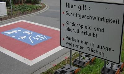 """Verkehrszeichen """"verkehrsberuhigte Zone"""" auf der Fahrbahn, daneben eine große Tafel, die verbal das Zeichen erklärt"""