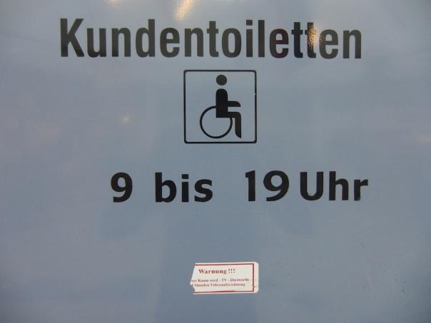 Beschriftung einer Tür: Kundentoilette mit einem kleinen Aufkleber darunter, der auf Videoüberwachung hinweist