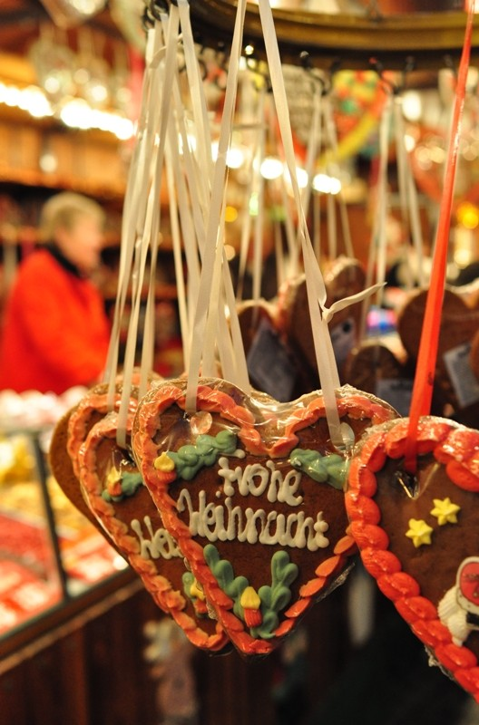 """Lebkuchenherzen mit der Aufschrift """"Frohe Weihnacht"""" an einem Weihnachtsmarktstand"""