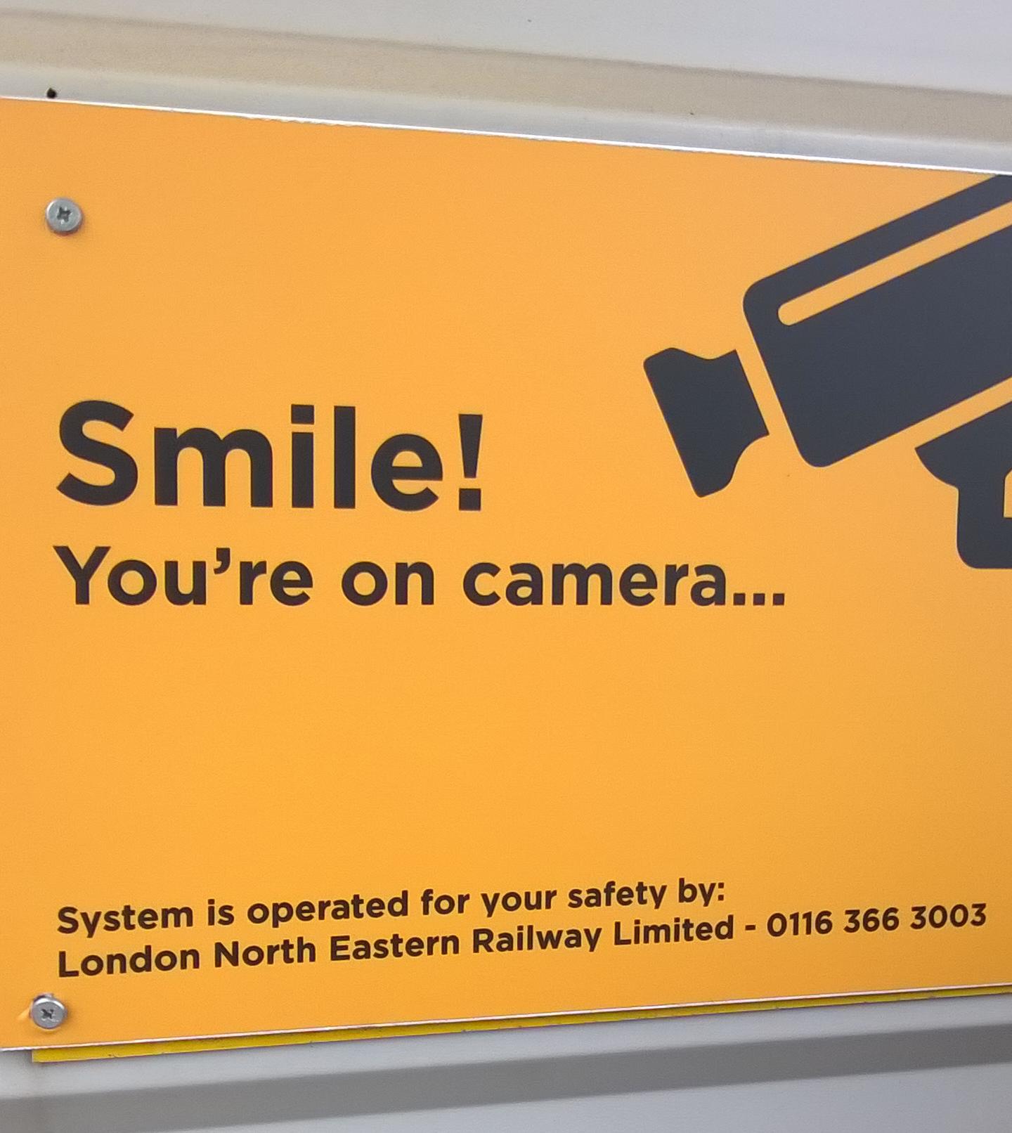 """Hinweisschild mit der Aufschrift: """"Smile, You're on camera…"""" auf einem Bahnhof in England"""